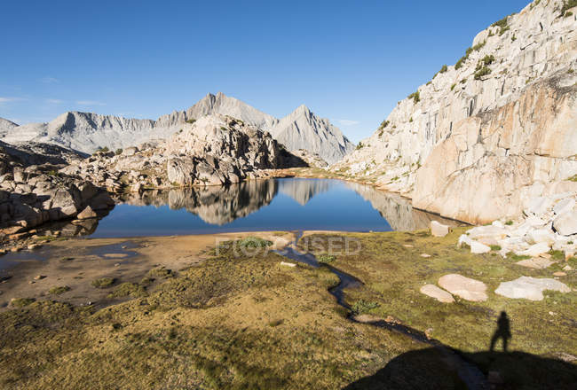 Shadow of hiker on grass with rocks reflecting in small pond — Stock Photo