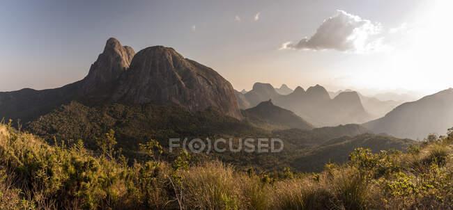 Bella vista alla grande cima rocciosa e altre montagne sulla foresta pluviale verde durante il tramonto, Rio de Janeiro, Brasile — Foto stock