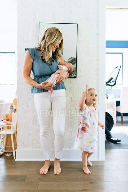 Retrato de la madre con su hija y su hijo recién nacido en casa - foto de stock