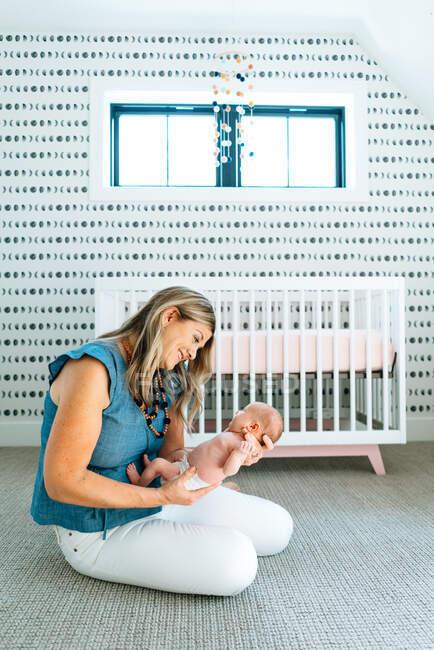 Retrato de la hermosa madre feliz y su hijo bebé en casa - foto de stock