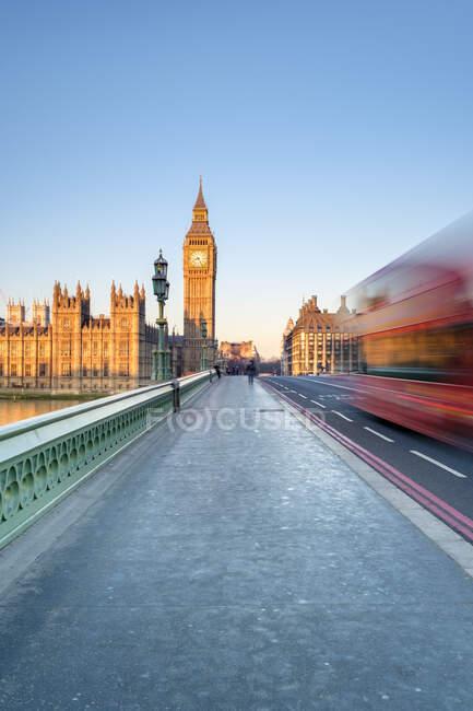 Красный двухэтажный автобус проезжает по Вестминстерскому мосту, перед Вестминстерским дворцом и часовой башней Биг-Бен (Башня Элизабет), Лондон, Англия, Великобритания — стоковое фото