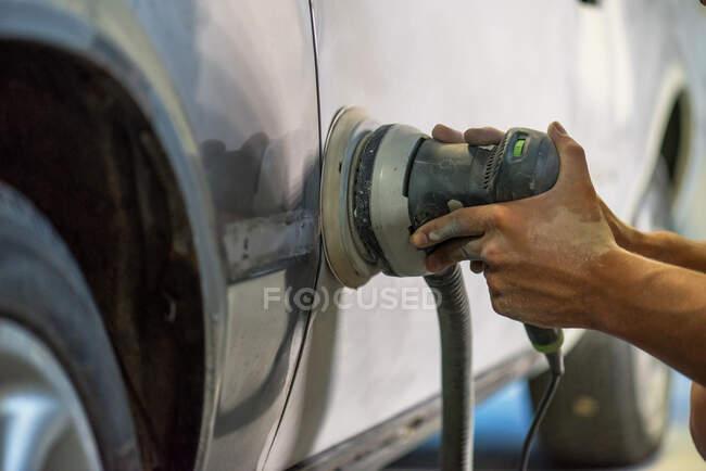 Schleifer in den Händen eines Mannes, der im Autohaus einen Autolack spitzt. — Stockfoto