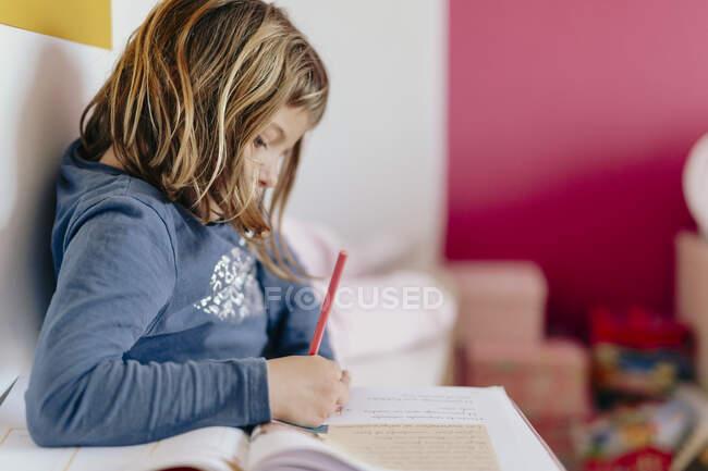 Mignonne fille en regardant ses devoirs — Photo de stock