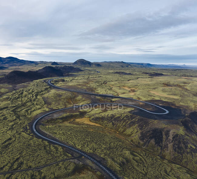 From above amazing landscape of empty curvy road running through green valley in Icelandic countryside under cloudy sky in sunny evening — Stock Photo