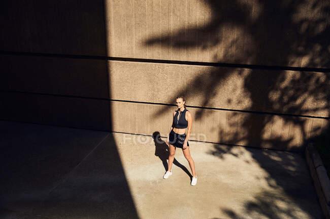 Retrato de hermosa mujer joven en ropa deportiva moderna con estilo posando en la calle de la ciudad - foto de stock