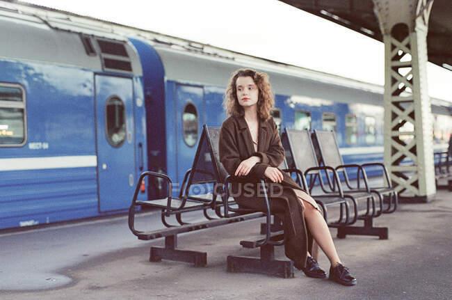 Eine Frau sitzt an einem Bahnhof in der Nähe eines Zuges — Stockfoto