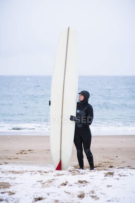 Молода жінка йде на серфінг у зимовий сніг. — стокове фото