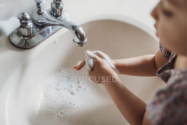 Niña lavándose las manos en el lavabo del baño con jabón. - foto de stock