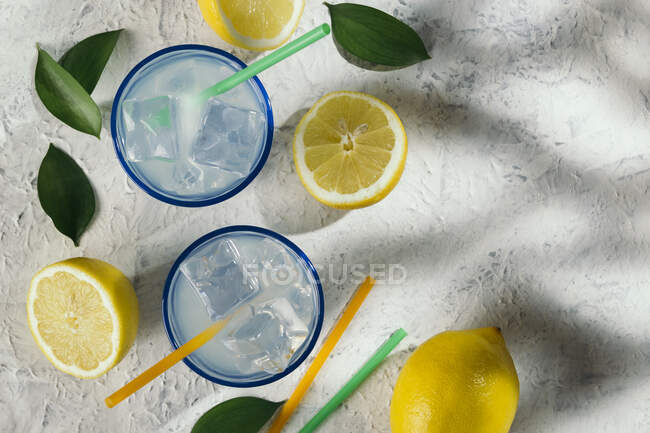Lemon juice glasses with ice and straws on a white table under the shade of a tree at an outdoor picnic. Refreshing, healthy, vitamin-rich drinks. — Stock Photo