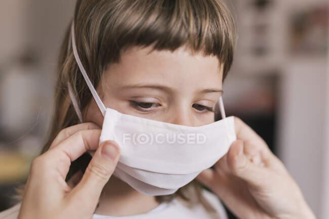 Mãe colocando máscara médica em sua filha para se proteger do coronavírus — Fotografia de Stock