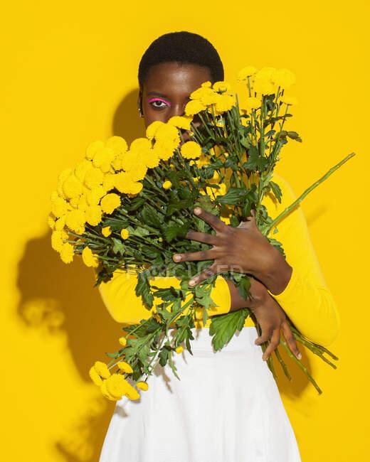 Attraktive schwarze Frau mit kurzen Haaren mit gelben Blüten auf gelbem Hintergrund — Stockfoto