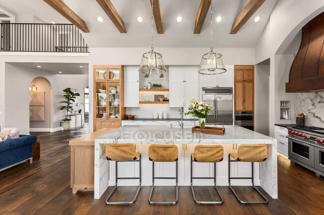 Kitchen в роскошном доме с большим островом и деревянными полами — стоковое фото