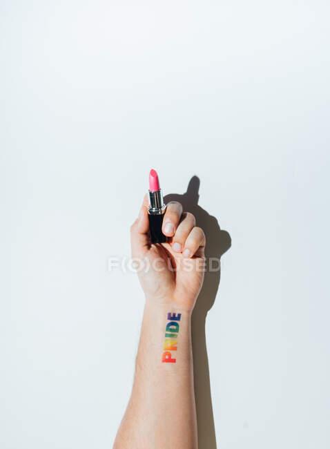 La mano de un gay con un tatuaje que dice orgullo y esmalte de uñas. Símbolo de liberación y tolerancia sexual. hah celebración de lápiz labial - foto de stock