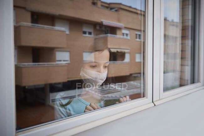 Menina com máscara facial olhando para fora da janela em quarentena em casa por covid-19 coronavirus pandemia — Fotografia de Stock