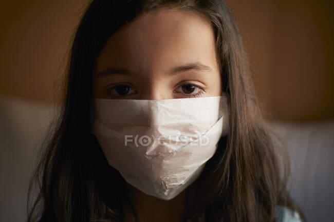 Menina com máscara facial em quarentena em casa para a pandemia do coronavírus covid-19 — Fotografia de Stock