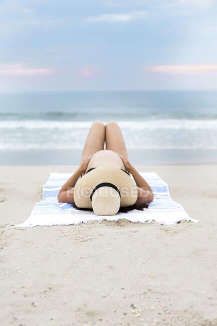 Mujer embarazada en bikini tendida en la playa - foto de stock