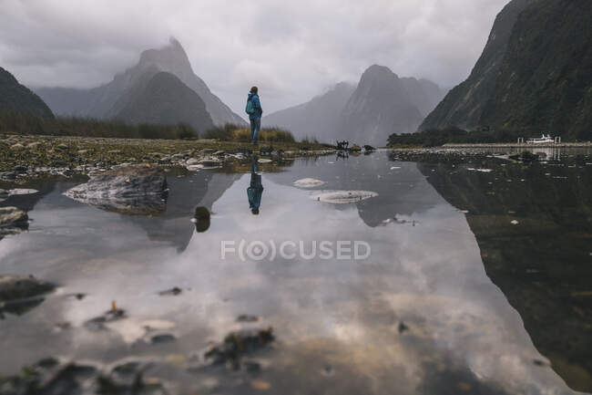 Young woman stands at the view of Mitre Peak in Milford Sound, New Zealand — Stock Photo