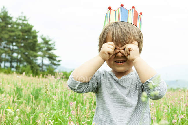 Little boy with a ccrown in meadow  covering his eye — Stock Photo