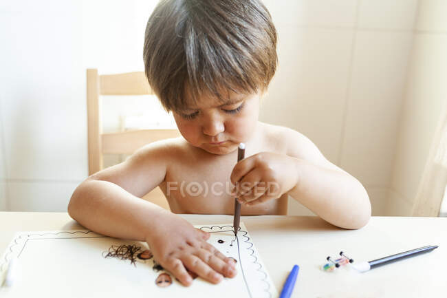 No shirt little boy sitting on table drawing at home — Stock Photo