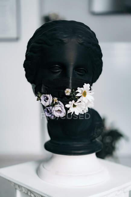 Schwarze Gips-Skulptur eines Frauenkopfes in schwarzer medizinischer Maske mit frischen Blumen — Stockfoto