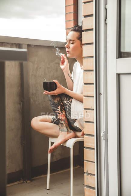 Menina em sua varanda casa com sua boneca durante o período de confinamento devido à epidemia de covid-19. — Fotografia de Stock