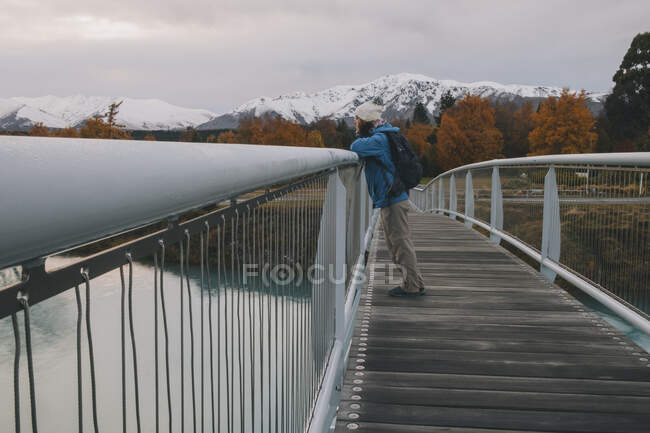 Woman looking at Lake Tekapo from bridge with mountains in background. — Stock Photo
