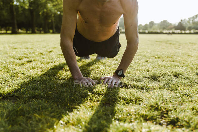 Man doing crunches outside on the grass — Stock Photo