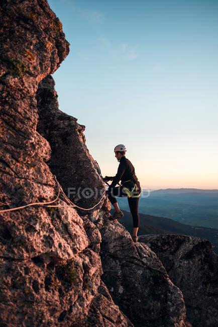 Mulher alpinista com capacete e arnês. Silhueta ao pôr-do-sol na montanha. Perfil. A descansar a olhar para a rota de escalada. Fazendo via ferrata nas montanhas. — Fotografia de Stock