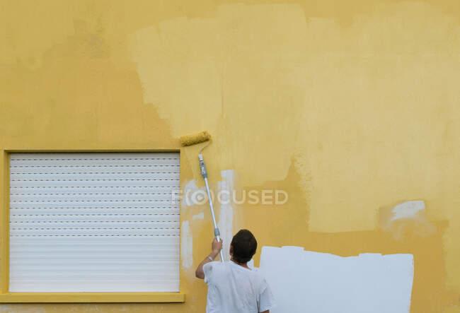 Maler streicht Hausfassade mit Walze gelb an — Stockfoto