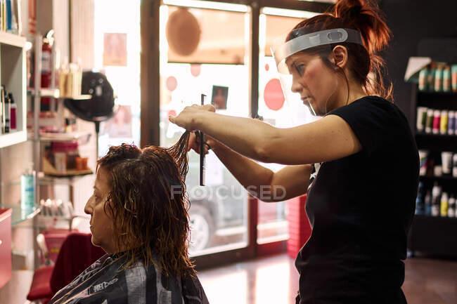 Parrucchiere taglia i capelli di un cliente con uno scudo viso — Foto stock
