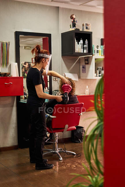 Parrucchiere con uno scudo viso asciuga i capelli del suo cliente — Foto stock