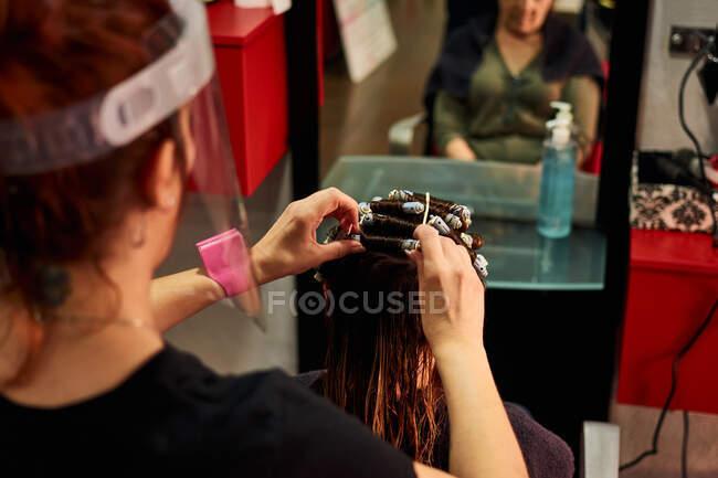 Un primo piano di un parrucchiere che pettina un cliente con uno scudo facciale — Foto stock