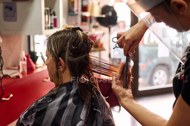 Un primo piano di un parrucchiere che taglia i capelli del cliente con uno scudo facciale — Foto stock