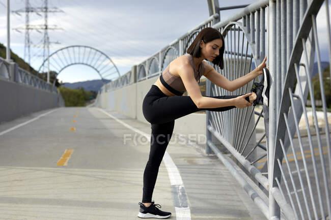 Полная длина женщины, растягивающей ногу во время тренировки на мосту — стоковое фото