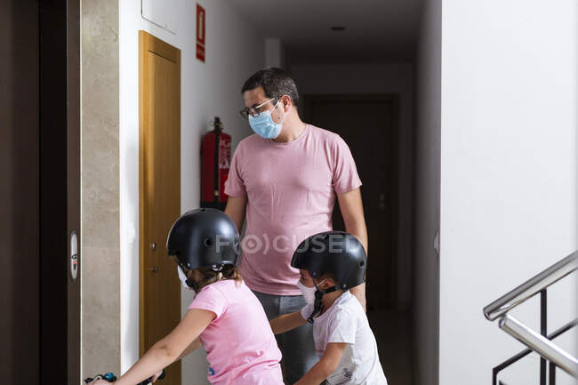 Family with medical masks and bicycles taking the elevator — Stock Photo