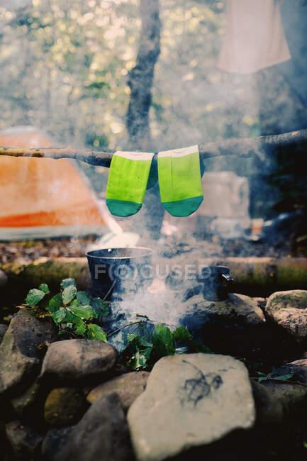 Secar los calcetines mojados en la hoguera durante el campamento. Calcetines secándose en el fuego. Descanso activo en el bosque. Aventura - foto de stock