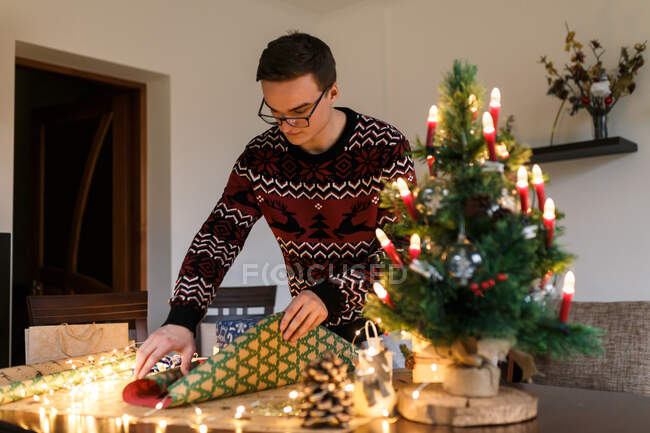 Young man packs Christmas presents for friends and family — Stock Photo