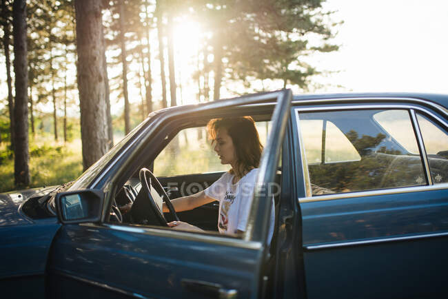 Woman sitting in a parked  broken car. — Stock Photo