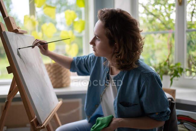 Focalizzato signora adulta utilizzando pennello per creare opere d'arte su cavalletto in laboratorio accogliente — Foto stock