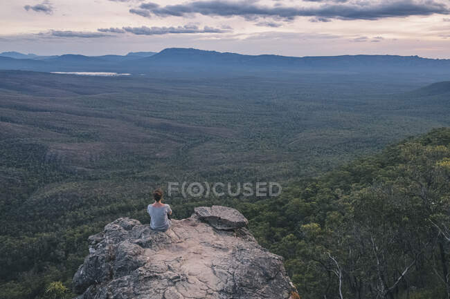 Young woman sits at the Balconies admiring the vast  landscape of Grampians National Park, Victoria, Australia — Stock Photo