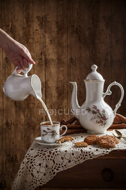 Hand pouring milk into coffee served on vintage tableware with homemade cookies on rustic table with a wooden background. — Stock Photo
