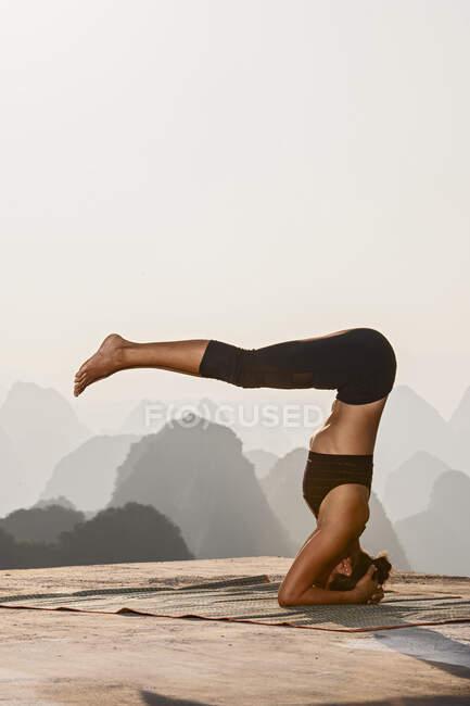 Молодая красивая женщина практикует йогу с видом на горы на заднем плане. — стоковое фото