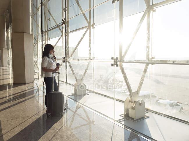 Mujer joven con maleta hablando por teléfono mientras espera el vuelo - foto de stock