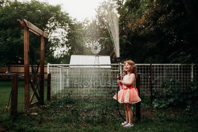 Маленька дівчинка в одязі поливає сад з водяним шлангом. — стокове фото