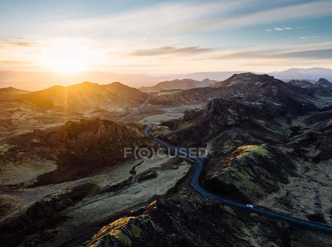 Чудовий вигляд звивистої дороги між скелястими горами на тлі заходу сонця в Рейк