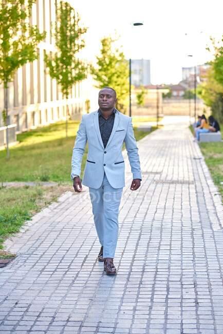 Elegante uomo d'affari che cammina per strada. Indossa abiti da lavoro ed è all'aperto. — Foto stock