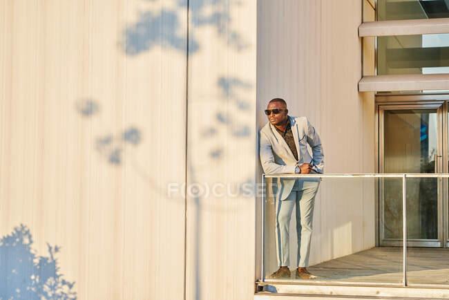 Empresário afro-americano ao pôr-do-sol num edifício. Ele está se aquecendo ao sol da noite. A sombra de uma árvore é projetada na parede — Fotografia de Stock