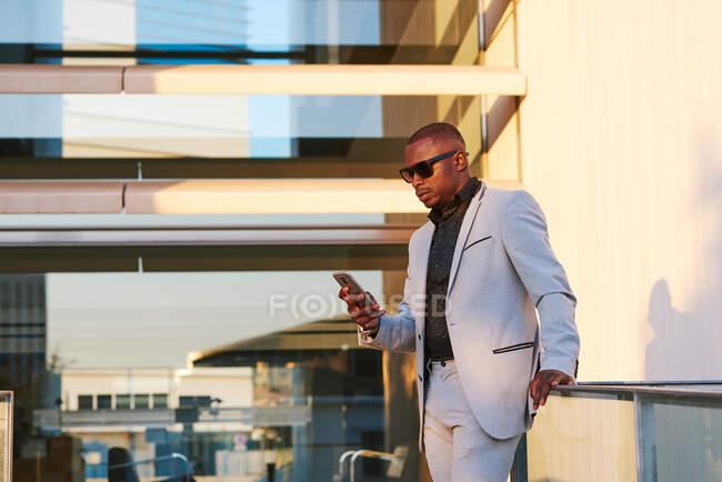 Homme d'affaires afro-américain avec téléphone portable un après-midi d'été. — Photo de stock