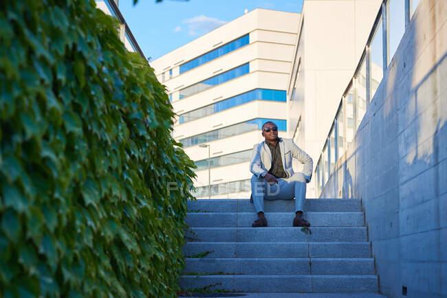 Elegante Afroamerikanerin sitzt auf den Stufen eines Parks. Er genießt die Abendsonne. — Stockfoto