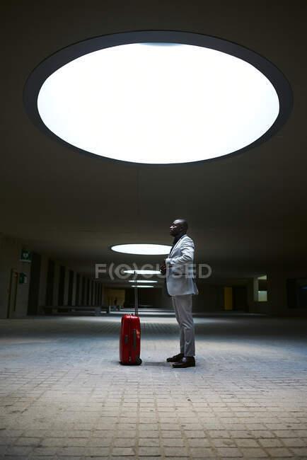 Афроамериканец с красным чемоданом. Он подсвечивается люком в здании — стоковое фото